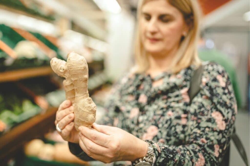 Frau kauft Ingwer im Supermarkt
