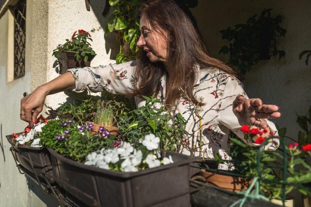 Frau pflegt Blumen auf Balkon
