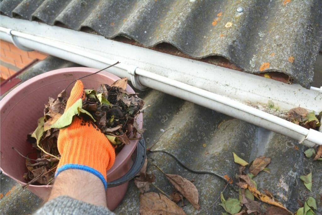 Hand stopft Laub aus Dachrinne in Eimer