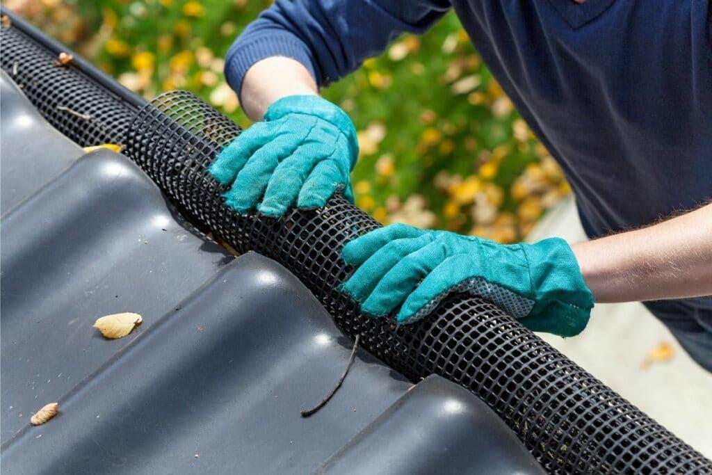 Mann bringt Dachrinnennetz zum Schutz vor Laub an