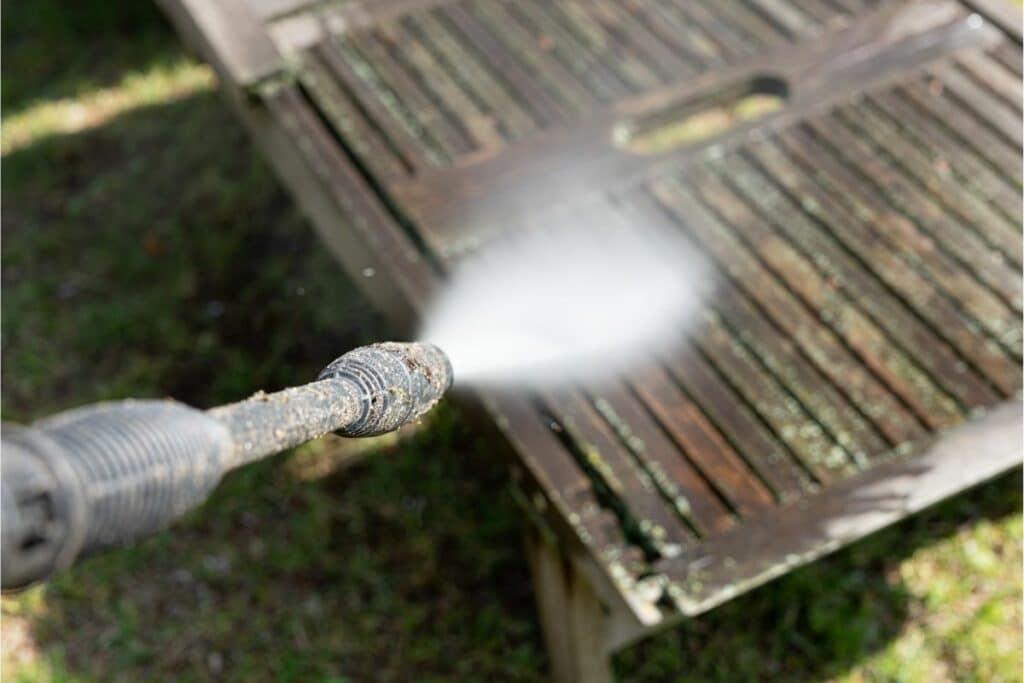 Grünbelag mit Hochdruckreiniger von Holztisch entfernen